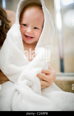 Mother drying off 1 year old baby girl after bath - Stock Photo
