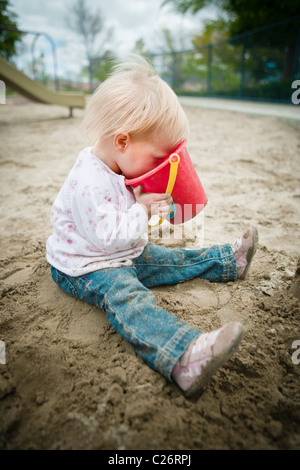1 Year old girl in Playground Sandbox Playing with Sand Toy - Stock Photo