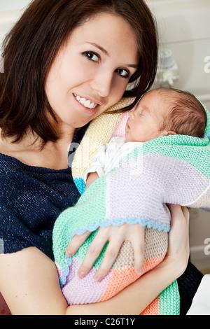 mum holding her premature baby boy - Stock Photo