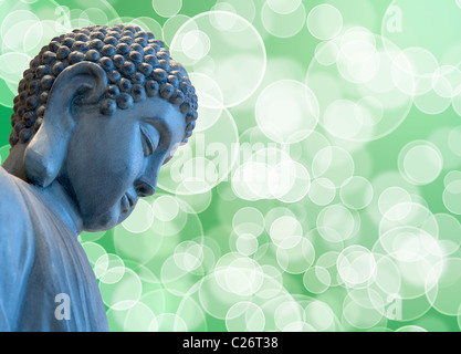 Bronze Zen Buddha Statue Meditating with Blurred Background - Stock Photo