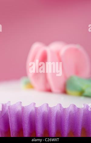Purple Cupcake with Pastel Pink Flower Decoration - Stock Photo