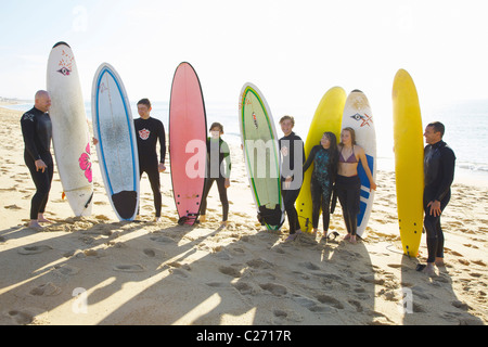 Group of Surfers Standing on Beach Holding Surfboards - Stock Photo