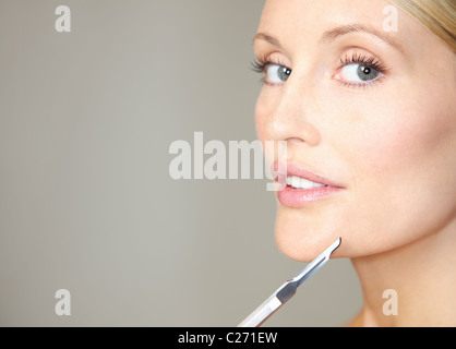 Woman Holding Surgical Scalpel in front of Face - Stock Photo