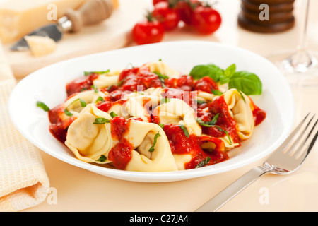 tortelloni pasta with tomato sauce and fresh basil - Stock Photo
