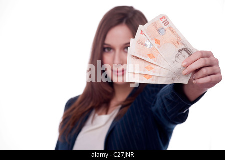 Brunette woman holding ten pound notes in her hand - Stock Photo