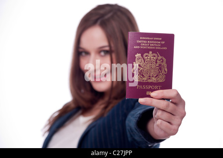 Brunette woman holding a British passport , going on holiday. - Stock Photo