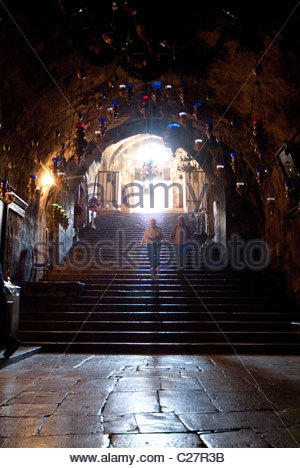 A couple descends into Mary's tomb on the Mount of Olives. - Stock Photo