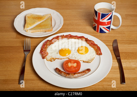 English fried breakfast in the shape of a human face with eggs for eyes, bacon for hair, sausage for mouth and tomato - Stock Photo