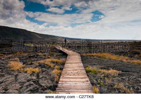 Two people walking on a wooden bridge over the Pu'uloa Petroglyphs. - Stock Photo