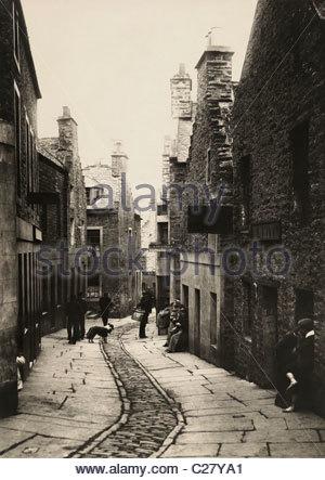 Locals talk on the narrow Bridge Street. - Stock Photo