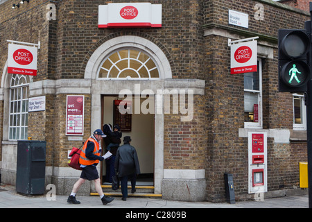 A post man walking past the Post office branch in Stoke Newington, Hackney, London. - Stock Photo