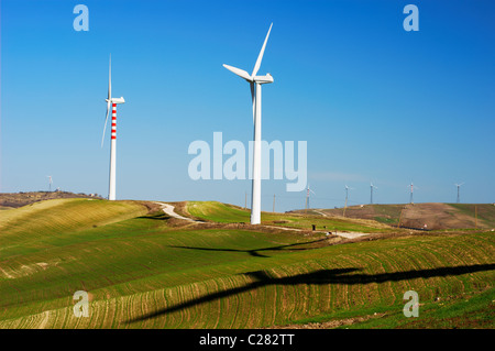 Vertical axis wind turbines and shadows on top of a hill - Stock Photo