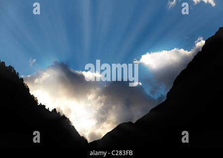 sun bursts through clouds from a dark mountain valley symbol for hope,call not to give up,light at the end of the - Stock Photo