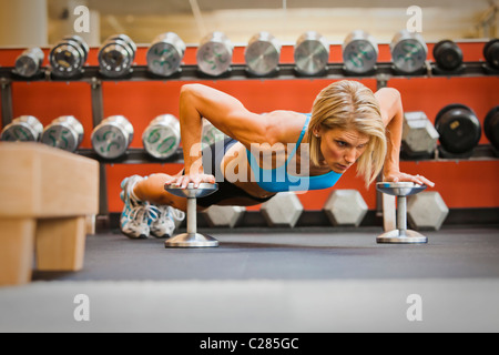 Physically fit woman doing pushups on dumbells in a healthclub. - Stock Photo