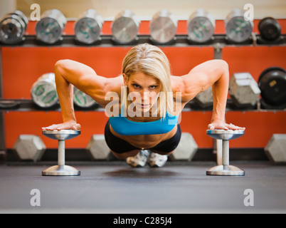 Physically fit woman doing pushups on dumbbells in a health club. - Stock Photo