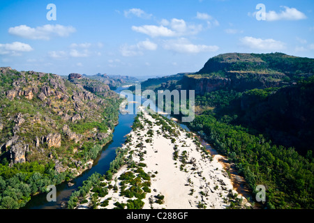 A river forks around a sand island in a rugged escarpment gorge. - Stock Photo