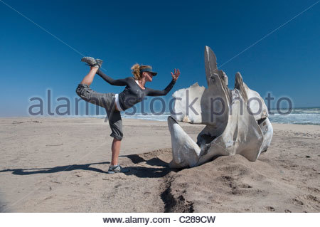 A woman does yoga on a beach next to a whale vertebra. - Stock Photo
