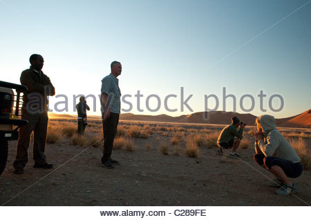 Tourists watch the sunset over the desert. - Stock Photo