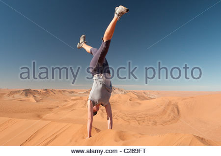 A woman does a hand stand on a sand dune in the Namib Desert, Namibia. - Stock Photo