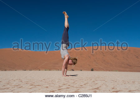 A woman does a handstand on a dry lake bed in a sand dune park. - Stock Photo