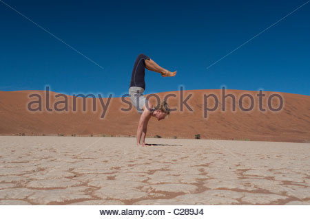 A woman does a handstand on a dry lake bed in Sossusvlei, Namibia. - Stock Photo