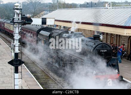 Steam locomotive pulls into the platform at Ramsbottom Station on the East Lancs Railway - Stock Photo