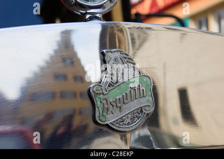 Maker's badge on the bonnet of an old Asquith vintage car with medieval buildings reflected in the chromework - Stock Photo