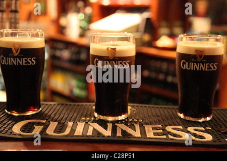 three pints of guinness partly filled standing on a bar counter inside an irish bar pub - Stock Photo