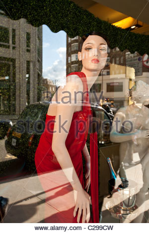 Reflection of a taxi in Harrods Department store window. - Stock Photo