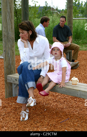 Unhappy housewife outside contemplating with little girl in playground and men talking behind her back. - Stock Photo