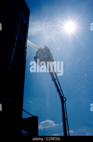Fireman spraying water from a hose mounted on a the ladder bucket of a fire truck - Stock Photo