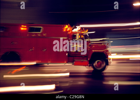 Blurred motion view of a fire truck racing to an emergency at night - Stock Photo