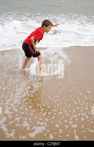 Boy playing on the sea shore evading incoming tidal waves. Sea Palling, Norfolk. - Stock Photo