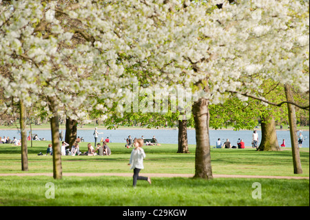 People relaxing by the side of the Round Pond in Kensington Gardens, London, England on a sunny spring day. - Stock Photo