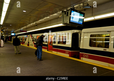 Commuters in motion blur boarding Translink Skytrain Vancouver Waterfront Station platform - Stock Photo