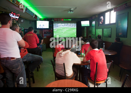 A group of men supporting Manchester United in a Maltese Bar - Stock Photo