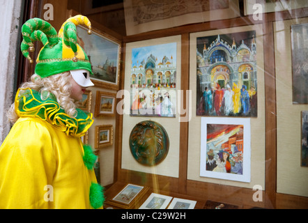 A girl in clown costume looks at paintings of Venice in a gallery window at the carnival, Venice, Italy - Stock Photo