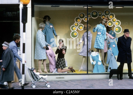 Vintage image of a young woman female shop assistant employee in the 1970s working as a window dresser looking out - Stock Photo