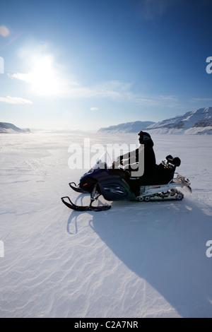 A snowmobile on frozen ice on a barren winter landscape - Stock Photo