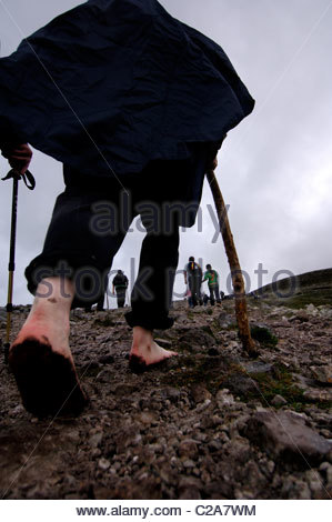 A pilgrim walking up Croagh Patrick with bare feet. - Stock Photo