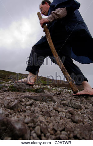 A pilgrim walking up a mountain in his bare feet. - Stock Photo