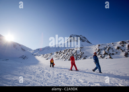Three people on a short mountain trek, against a beautiful winter landscape - Stock Photo