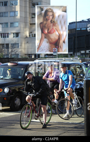 cyclist and car's  waiting at red  traffic light  M&S advert in the background London England - Stock Photo