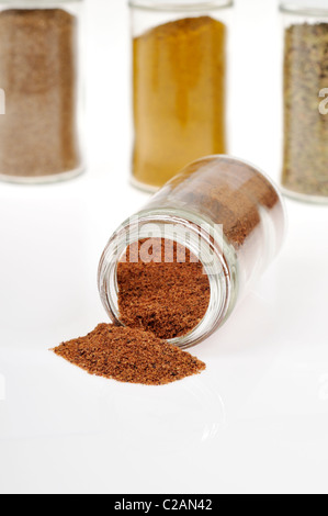 Bottle of the spice nutmeg on its side with nutmeg spilled out with other spice and herb bottles in background on - Stock Photo
