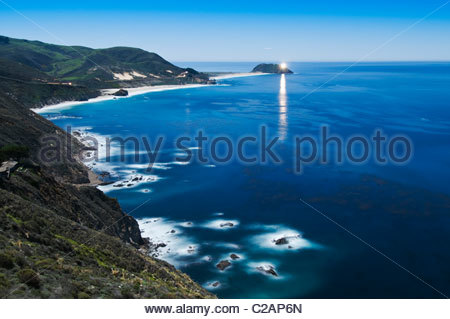 Highway 1, Big Sur coast, and Point Sur Lighthouse under a full moon. - Stock Photo