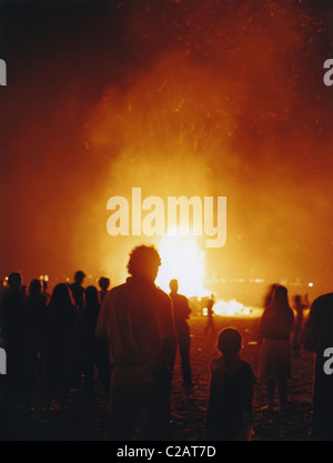 Crowd of people watching New Year's Eve bonfire on beach, Salinas, Ecuador - Stock Photo