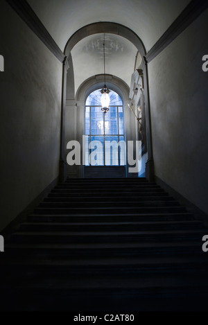 Stairwell leading up to paned window, lamp hanging from vault ceiling - Stock Photo