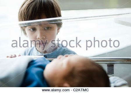 Young boy staring at newborn sibling in hospital crib - Stock Photo