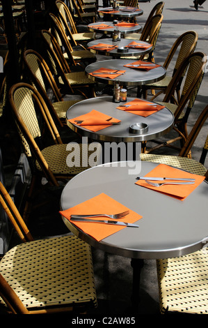 Tables set with napkins and utensils in sidewalk cafe - Stock Photo
