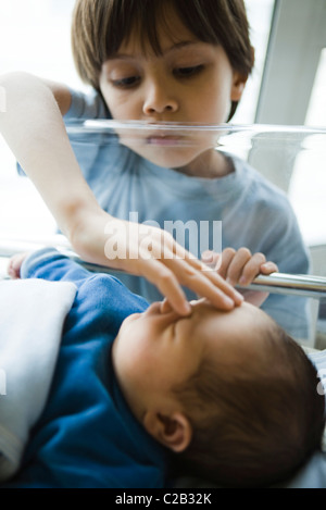 Young boy looking down at newborn sibling and touching its forehead - Stock Photo
